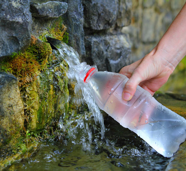 filling water bottle from spring